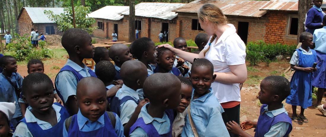 Volunteer surrounded by smiling schoolchildren